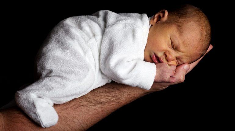 recien nacido durmiendo en el brazo de su padre